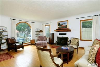 This large formal living room has coved ceilings and hardwood fl